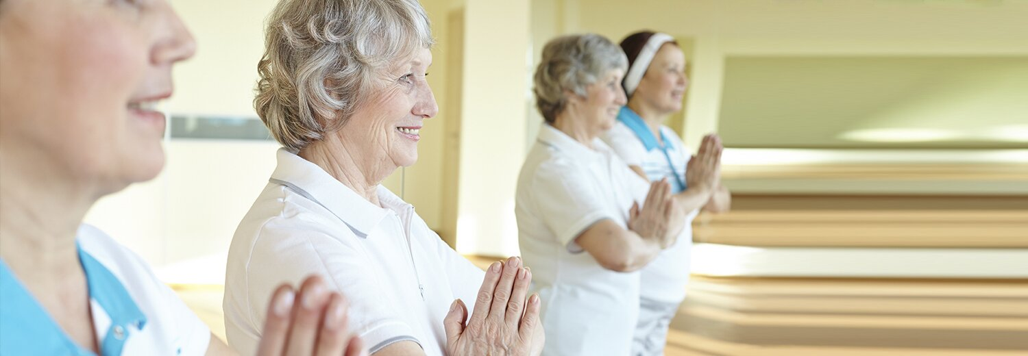 four older woman doing yoga, standing up with hands in a prayer position