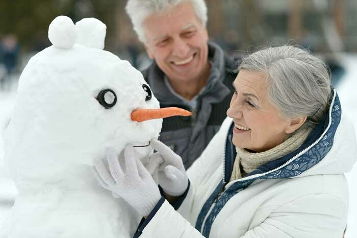 An older man and woman building a snowman