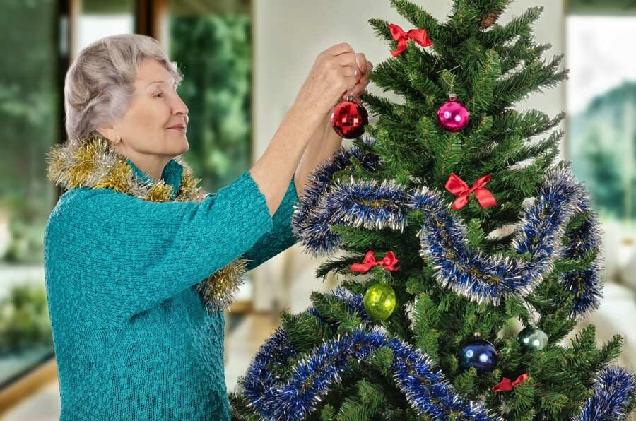 Senior woman decorating Christmas tree