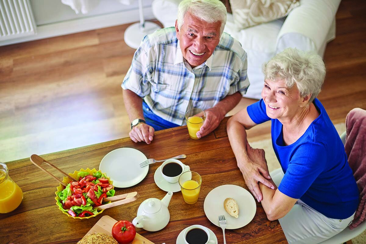 Older couple eating healthy meal with salad and juice